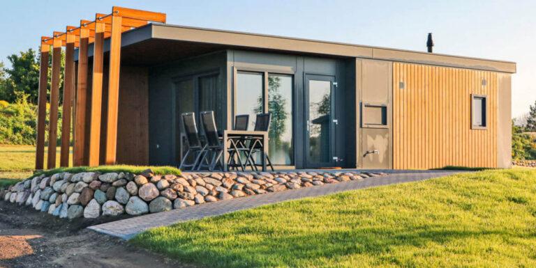 modernes Chalet in Süsel Seeparx aus hellem Holz kombiniert mit Grauen Wandelementen,bodentiefer Fensterfront sowie teilüberdachter Terrasse, Tisch und vier Stühlen