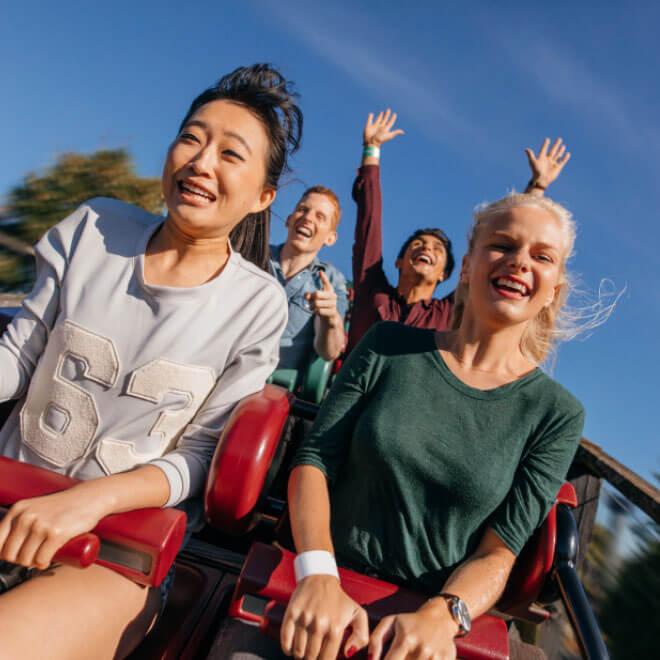 Zwei junge Frauen und dahinter zwei junge Männer beim Achterbahn fahren vor blauem Himmel im Hansapark Sierksdorf