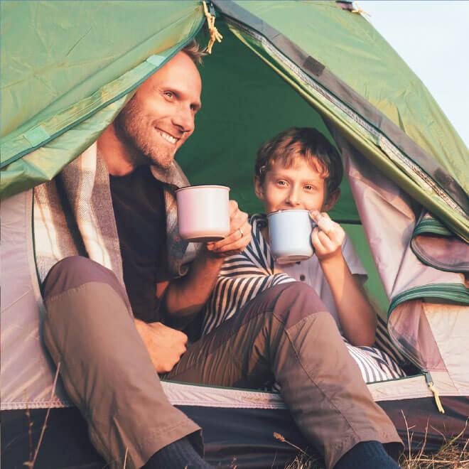 Süsel Seeparx Camping Platz - Papa und Sohn sitzen im Zelteingang und trinken aus Bechern