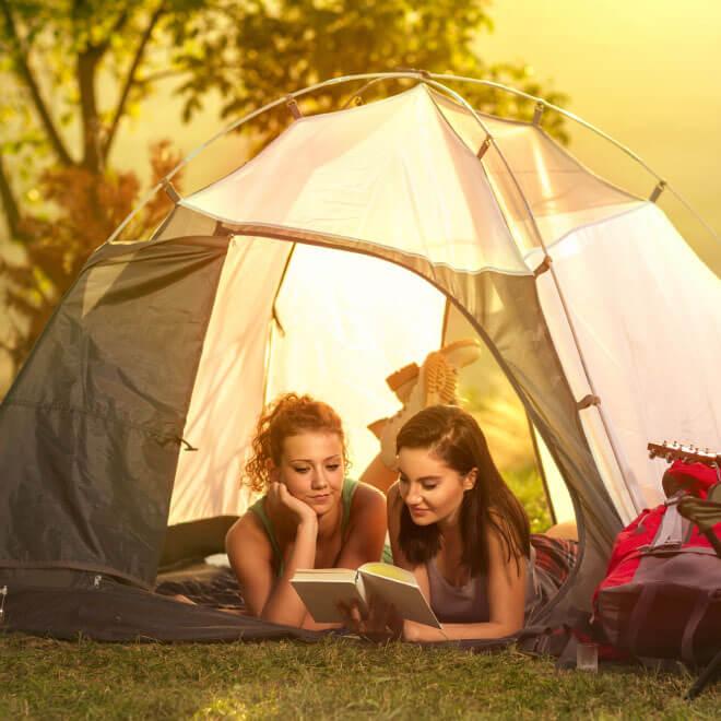 Süsel Seeparx Camping Platz - 2 junge Frauen lesen im Zelt am See