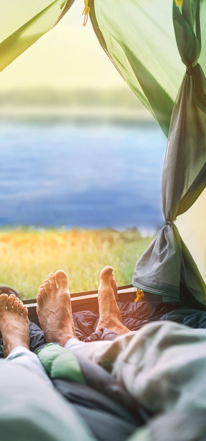 Süsel Seeparx Camping Platz - Blick auf die Füße im Zelteingang und das Seeufer Süsel