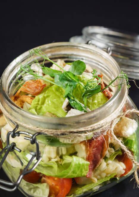 mediterraner Salat mit getrockneten Tomaten, Kräutern und Fata-Käse in einem Einmachglas