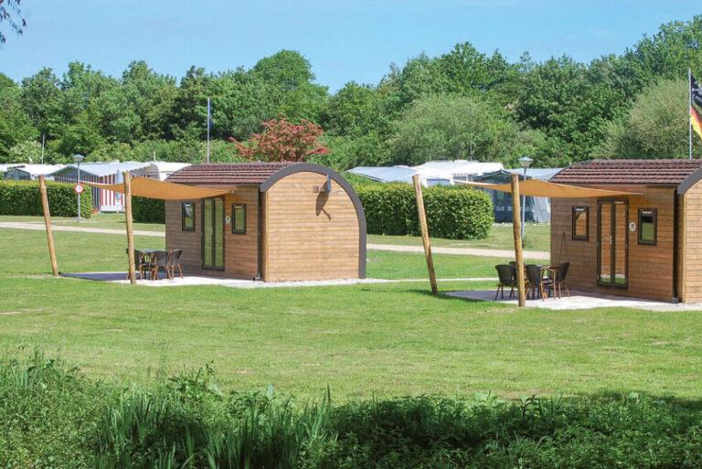 Zwei SeeLodges im Sonnenlicht auf der grünen Rasenfläche des Campingplatzes mit Holzwänden, einem runden Dach, 2 kleinen Fenstern und eine doppelflügelige Glastür, davor jeweills eine gepflasterte Terrasse mit Tisch, vier Stühlen und Sonnensegel