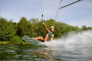 Süsel Seeparx - Wakeboarderin dicht über dem Wasser in den Knien