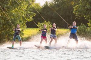 Süsel Seeparx - 4 vier Wakeboarder gleichzeitig nebeneinander auf dem Wasser mit grüner Wiese und baumbewachsenen Ufer im Hintergrund