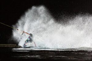 Süsel Seeparx Wakeboard Park - Wakeboarder im Dunklen angeleuchtet, spritzende Wasserfontäne