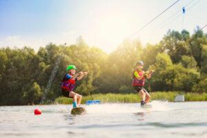 Süsel Seeparx - Zwei Kids beim Wakeboarden nebeneinander auf dem See, im Hintergrund strahlt die Sonne durch die Blätter der Bäume am Ufer