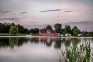 Blick über den See Süsel Seeparx im rosa Morgenlicht auf das Haus, die Seeterrasse und den Start einer Seilbahn sowie ein Feature
