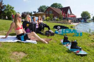 Süsel Seeparx - Wakeboarderinnen entspannen und sonnen sich auf der Liegewiese am See neben der Seeterrasse und dem Backsteinhaus mit Bistro