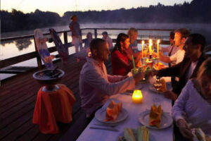 Süsel Seeparx - Firmenfeier auf der Seeterrasse bei Kerzenlicht und eingedecktem Tisch, im Hintergrund der See in Abendstimmung mit aufkommendem Nebel