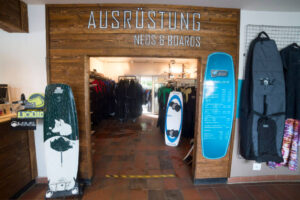Süsel Seeparx Wakeboard Store Eingang mit Wakeboards und zugehörigen Taschen, Blick durch den Eingang auf Kleiderstangen mit Neoprenanzügen
