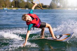 Süsel Seeparx - Junge auf dem Wakeboard lehnt sich über die Seite tief dem Wasser entgegen und streift mit der Hand beim Fahren das Wasser