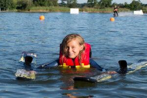 Süsel Seeparx - junges Mädchen mit Wakeboard im Wasser beim Schwimmen an Land
