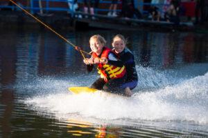 Zwei strahlende Mädchen knien auf dem Kneeboard bei voller Fahrt und spritzendem Wasser