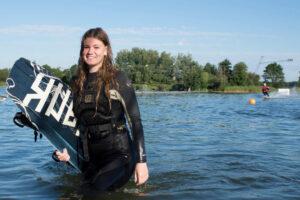 Süsel Seeparx - Wakeboarderin auf dem Weg aus dem Wasser raus mit dem Wakeboard unter dem Arm