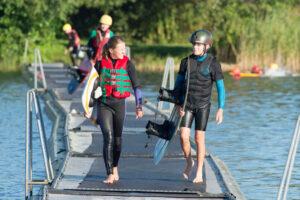 Wakeboarder gehen über den Steg und sind auf dem Weg zur Seilbahn