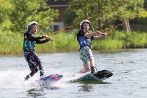Süsel Seeparx Wakeboard Park - 2 Kids beim Wakeboarden zusammen auf dem Wasser