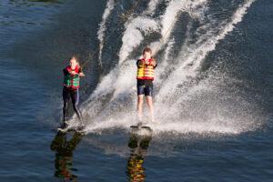 Zwei Kinder beim Wasserski Fahren nebeneinander auf dem See im Sonnenlicht
