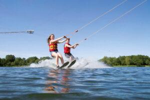 zwei Jungendlichen beim Wasserski-Fahren nebeneinander bei strahlend blauem Himmel